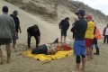 Rescuers stand with a pigmy killer whale after it was transported to Rarawa Beach from Ninety Mile Beach in the far north of the North of New Zealand. Another 50 whales beached themselves on Friday. Photo: AP