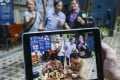 Masaki Fujihata's augmented reality app in action. Toon Lai-ning, 66, (back, left) and Jannie Wong Yuk-chun, 69, (back, right) lived in Wan Chai for decades and they shared their stories with Fujihata (back, centre) for him to create the AR figures. Photo: Dickson Lee