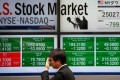 A man walks past an electronic board showing US stock market indicators outside a brokerage in Tokyo. Asian equities fell on Wednesday following a slump in US markets. Photo: Reuters