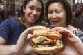 SCMP reporters Alkira Reinfrank (left) and Bernice Chan try the cheeseburger at Five Guys in Wan Chai. Photo: Jonathan Wong