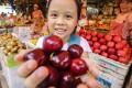 Schoolgirl Chloe Lam shops for cherries at the Yau Ma Tei fruit market. American-grown cherries have fallen in price in Hong Kong since tariffs were imposed on them on the mainland. Photo: Dickson Lee