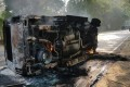 An upturned, smouldering vehicle in the aftermath of mob violence at Chingravati village. Photo: AFP