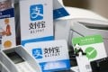 Signs for Ant Financial Services Group's Alipay, an affiliate of Alibaba Group Holding and Tencent's WeChat;