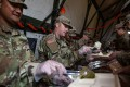 US Army soldiers during a Thanksgiving meal on the US-Mexico border in Donna, Texas. The US this week will begin withdrawing many of the active duty troops there. Photo: AFP