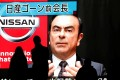 Passers-by in Tokyo watch coverage of Carlos Ghosn's indictment. Photo: Reuters