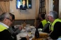Yellow vest protesters take notes as they watch President Emmanuel Macron's speech on television on Monday. Photo: AFP