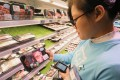 A shop assistant looks at packaged meat in a Hema Supermarket in Shanghai on November 10, 2018. Photo: SCMP/Simon Song
