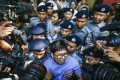 Reuters journalists Wa Lone (centre front) and Kyaw Soe Oo (centre back) as they leave the court after their first trial in Yangon. Photo: EPA