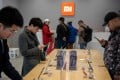 Customers look at mobile phones in a Xiaomi shop in Beijing on November 7, 2018. Photo: AFP