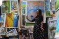 Chinese artist Ma Chunyan, 32, reproduces a masterpiece from an image of the original displayed on her mobile phone at her studio in Dafen Oil Painting Village in Shenzhen, Guangdong province. Photo: Reuters