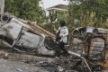 A journalist walks by a burnt car that was flipped upside down during a riot at the Seafields temple. Photo: EP