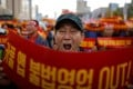 "A taxi driver takes part in a protest against a carpool service application that will be launched by Kakao Corp later this year, in central Seoul, South Korea, October 18, 2018. The banners read, ""Stop carpool service application, it is illegal business"". Photo: Reuters"