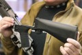 A bump stock device (right), that fits on a semi-automatic rifle to increase the firing speed, making it similar to a fully automatic rifle, is shown next to a AK-47 semi-automatic rifle at a gun store in Salt Lake City, Utah. Photo: Agence France-Presse