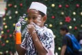 A Muslim boy blows bubbles in front of a Christmas tree in Kuala Lumpur, Malaysia. Photo: AP