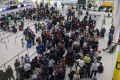Passengers queue in the departures hall of the South Terminal at London Gatwick Airport on Friday. Photo: Xinhua