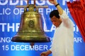 Raising a clenched fist, Philippine President Rodrigo Duterte rings one of the Balangiga church bells during a ceremony on December 15. Photo: AFP