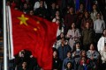 Chinese citizens look at their flag as they sing their national anthem during the opening ceremony of the FINA Swimming Short Course World Championships in Hangzhou on December 11. Photo: EPA-EFE