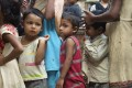 Orphaned children in Nepal line up for a meal.