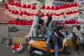 Indian vendors sell Santa Claus masks and caps on a street in Hyderabad, India. Photo: AP