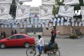 A rickshaw driver cycles past a street adorned with election posters in Dhaka. Photo: AFP