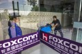 A security guard stands at the front doors of the Foxconn factory in Guiyang, Guizhou Province, China. Photo: EPA-EFE