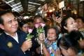 Thai junta leader Prayuth Chan-ocha receives flowers from supporters. Photo: EPA