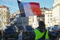 """A protestor wearing a """"yellow vest"""" (gilets jaunes) and brandishing a French national flag stands in front of riot police armoured vehicles in Marseille during a protest against rising costs of living on December 8, 2018. Photo: AFP"""