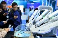 Visitors watch a robot performing surgery during the 2018 national mass innovation and entrepreneurship week in Beijing in October. Photo: Xinhua