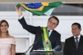 Brazil's new President Jair Bolsonaro (centre) waves a national flag while addressing supporters flanked by First Lady Michelle Bolsonaro and Brazil's new Vice-President Hamilton Mourao, during their inauguration ceremony at Planalto Palace in Brasilia on Tuesday. Photo: Agence France-Presse