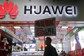 A worker at a retail shop in Shenzhen promotes Huawei 5G products. Photo: AP