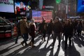 Pedestrians pass in front of an illuminated American flag in the Times Square neighborhood of New York, U.S., on Monday, Dec. 17, 2018. Health-care and technology stocks pushed U.S. equity indexes lower as investors considered the impact of the Federal Reserve on growth in an economy already jittery over trade, political tensions and a possible government shutdown. Photo: Michael Nagle/Bloomberg