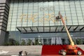 Workers remove the title of Dolce & Gabbana's fashion show at the Shanghai Expo Centre on November 22, after the show was cancelled in the wake of a Chinese backlash against the fashion brand's perceived racism. Photo: Reuters