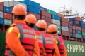 Employees look at a cargo ship at a port in Qingdao, east China's Shandong province on November 8, 2018. Photo: Agence France-Presse/China OUT