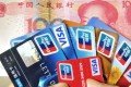 A Chinese woman poses with a handful of credit cards and a 100 yuan banknote Beijing . Photo: AFP
