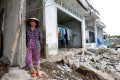 A woman stands at her collapsed house damaged by landslide along Mekong river in Can Tho city, Vietnam. Photo: Reuters