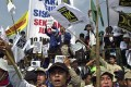 """Demonstrators in Jakarta chant Islamic religious songs and wave banners reading """"Save the religious community from apostasy"""". Photo: AFP"""