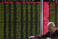 A stock brokerage in Beijing on November 20, 2018. Contrary to global conventions, China's stock exchange depicts gains and advances in red, using green to represent loses and declines. Photo: SCMP/ Simon Song