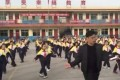 School principal Zhang Pengfei leads the dance routine in front of Xi Guan Primary School. Photo: Handout