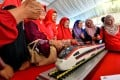 People pose with a model train at the launch of the East Coast Rail Link project in Kuantan, Malaysia, in August 2017. Photo: Xinhua