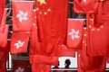 People walk past a display of China's national flags and those of Hong Kong, ahead of the 20th anniversary of the city's handover from Britain to China. Photo: AFP