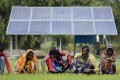 Indian farmers work near a newly installed water pump that relies on solar power. Photo: EPA