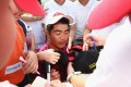 Chinese player Liang Wenchong signs autographs for students during the first round of the 2014 Hong Kong open, at The Hong Kong Golf Club in October 2014. Photo: Handout