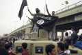 Islamic State group militants hold up their flag as they patrol in a commandeered Iraqi military vehicle in Fallujah, Iraq. Photo: AP