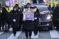 A mourner with a portrait of the deceased Kim Bok-dong. Photo: AP
