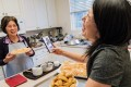 Lisa Lin recording a video of her 73-year-old mother describing the savoury fried butterfly crackers she has just cooked. Photo: Nick Otto for The Washington Post