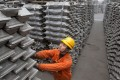 An employee checks aluminium ingots for export at the Qingdao Port, Shandong province March 14, 2010. REUTERS/Stringer/File Photo CHINA OUT. NO COMMERCIAL OR EDITORIAL SALES IN CHINA