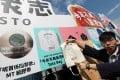 Activist Joshua Wong Chi-fung poses with a tote bag at the Demosisto stall in Victoria Park. Photo: Felix Wong