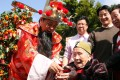 "The ""God of Fortune"" delivers a red packet (lai see) to 100-year-old Cheung Yuen-kiu, as hundreds of elderly people tie their New Year wishes to a tangerine tree at Wong Tai Sin Temple. Photo: Oliver Tsang"