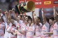 England's Tom Mitchell (centre) hoists the trophy as he and his teammates celebrate after defeating South Africa to win the 2017 World Rugby Sevens Series event in Vancouver. Photo: AP