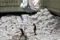 Workers unload imported rice in Manila. Photo: Reuters
